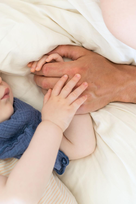 Einschlafbegleitung: Vater hält die Hand des schlafenden Babys www.chezmamapoule.com