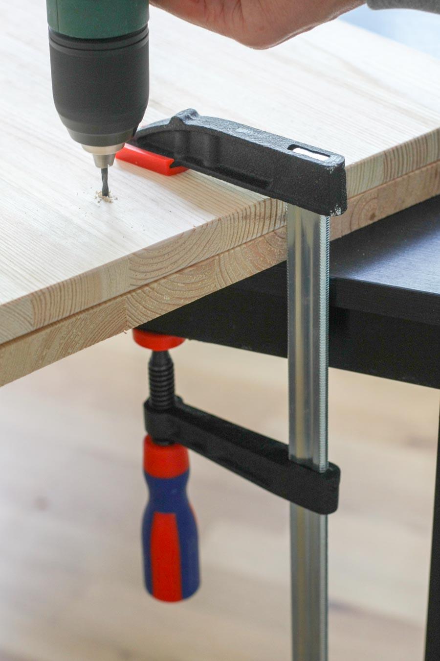 2. Bohren Mithilfe der Zwinge und einem alten Brett als Unterlage bohren, so splittert das Holz am Bohrausgang weniger