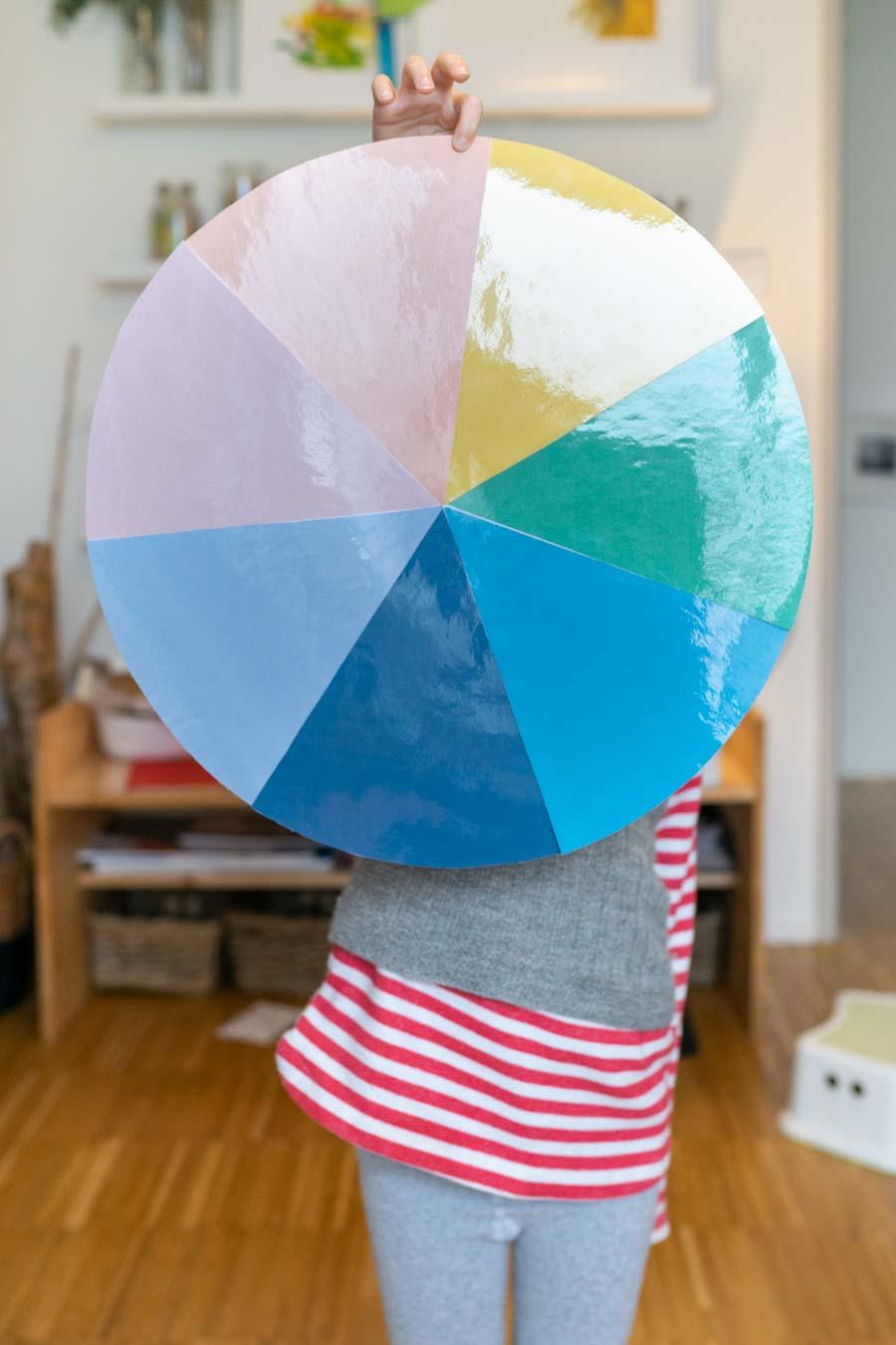 Ein Kind hält einen bunten Kreis hoch