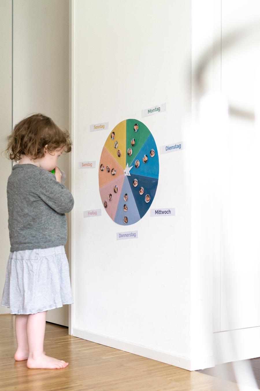 Ein Kleinkind steht vor einem Wochenplan, der an der Wand angebracht ist