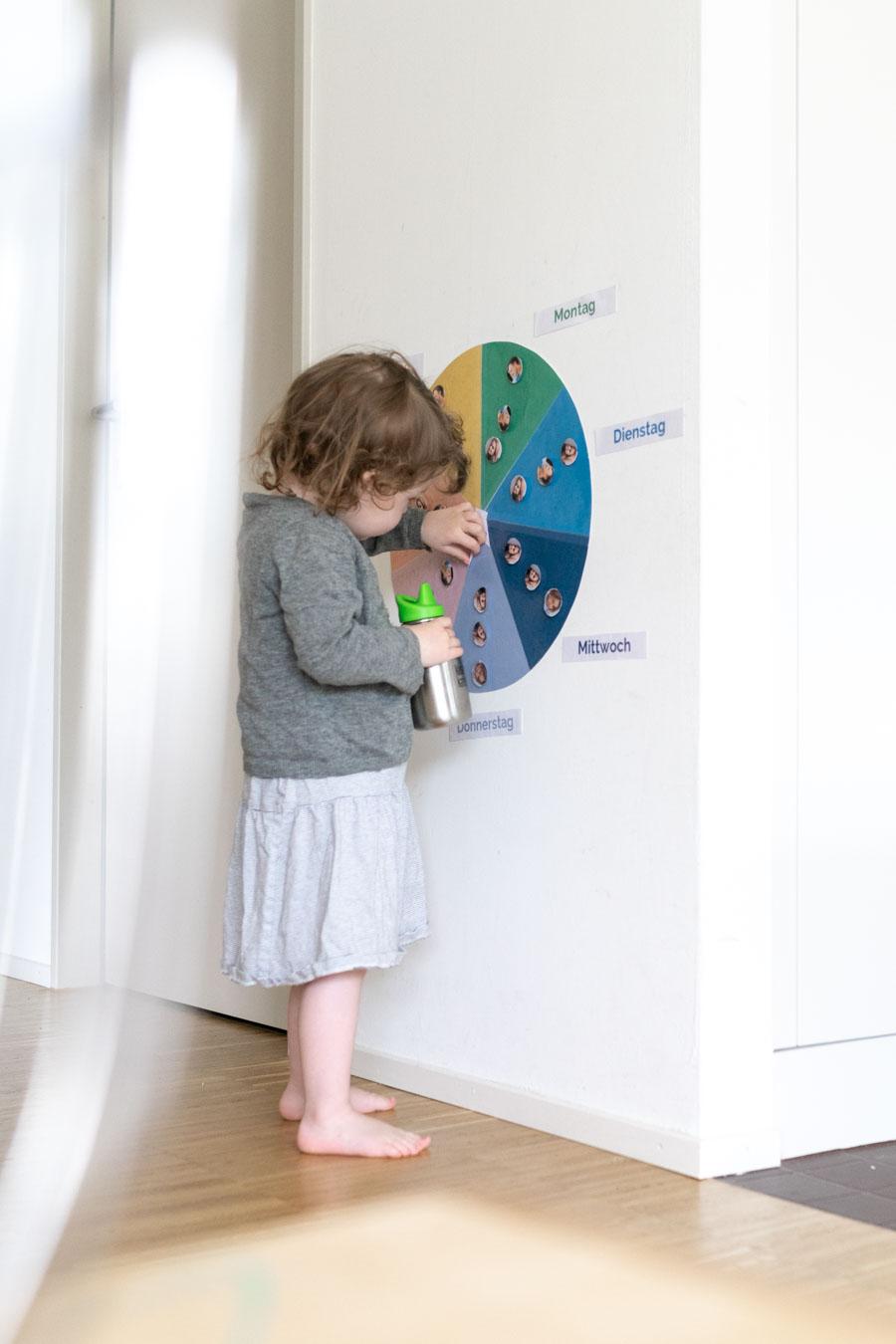 Ein Kleinkind sieht sich einen Wochenplan an