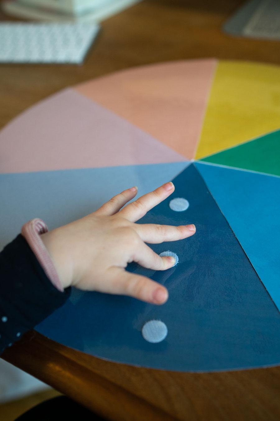 Ein Kind bringt selbstklebende Klettpunkte von Tesa an