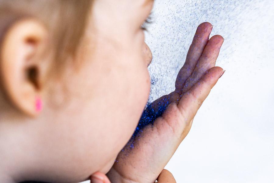 Kind pustet Glitzerstaub - ähnlich verbreiten sich Viren